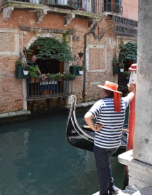 A gondolier talking with a waiter across the canal