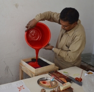 The pigment being poured into the tray for printing.
